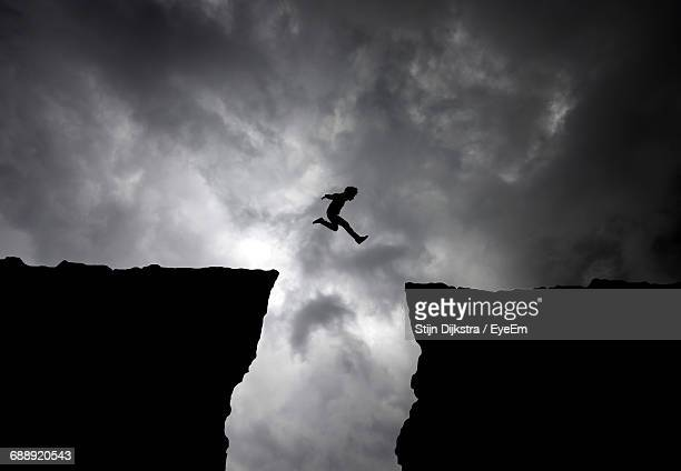 silhouette man jumping over cliffs against cloudy sky - risque photos et images de collection