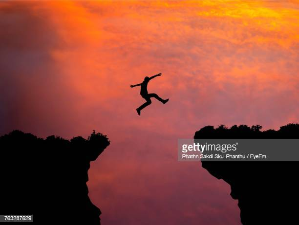 Silhouette Man Jumping Over Cliffs Against Sky During Sunset