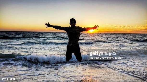 silhouette man jumping over shore at beach against sky during sunset - arms outstretched stock pictures, royalty-free photos & images