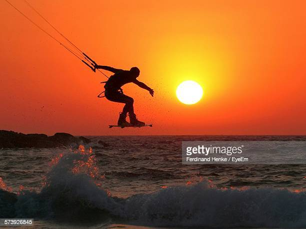 silhouette man kiteboarding over sea against sky during sunset - kiteboarding stock photos and pictures