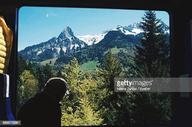 Silhouette Man Looking At Trees On Mountain Against Clear Sky Through Train Window