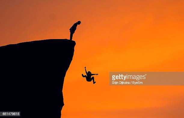 silhouette man looking at woman falling from cliff against clear orange sky - cliff stock pictures, royalty-free photos & images