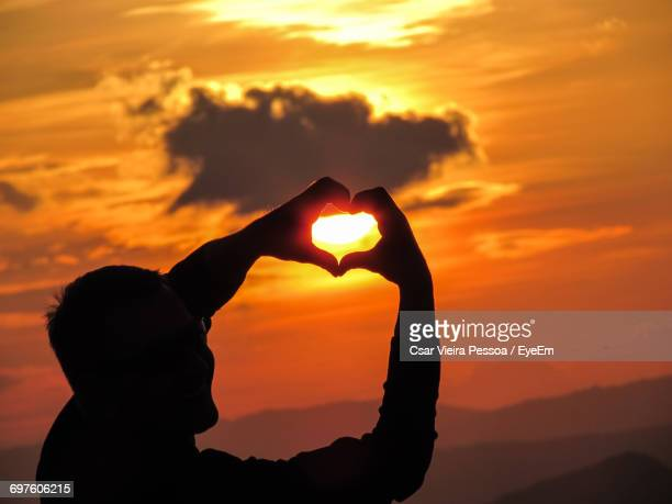 Silhouette Man Making Heart Shape With Hands Against Sky During Sunset