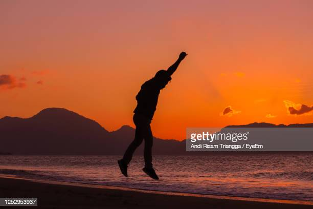 silhouette man on beach against orange sky - banda aceh stock pictures, royalty-free photos & images