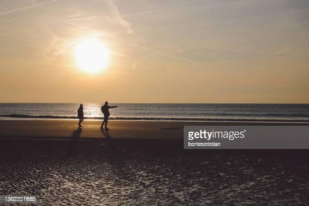 silhouette man on beach against sky during sunset - bortes stock-fotos und bilder