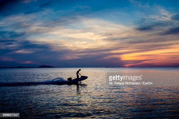 Silhouette Man On Jet Boat In Sea Against Cloudy Sky During Sunset