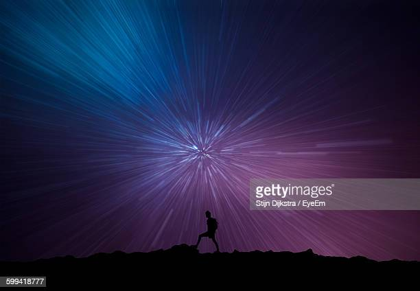 Silhouette Man On Landscape Against Starry Sky