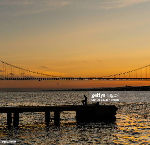 Silhouette Man On Pier Over Tagus River Against Sky During Sunset
