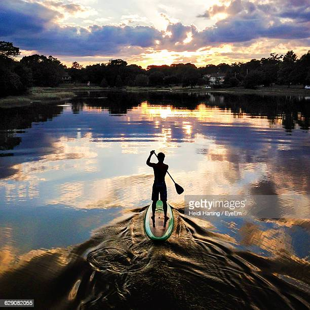 Silhouette Man Paddleboarding In Lake Against Sky During Sunset