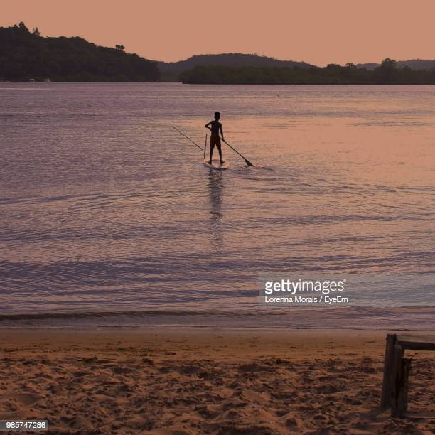 silhouette man paddleboarding on lake during sunset - lorenna morais - fotografias e filmes do acervo