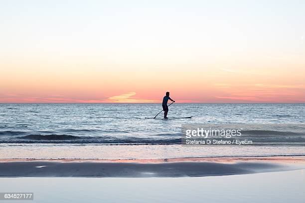 Silhouette Man Paddleboarding On Sea At Sunset