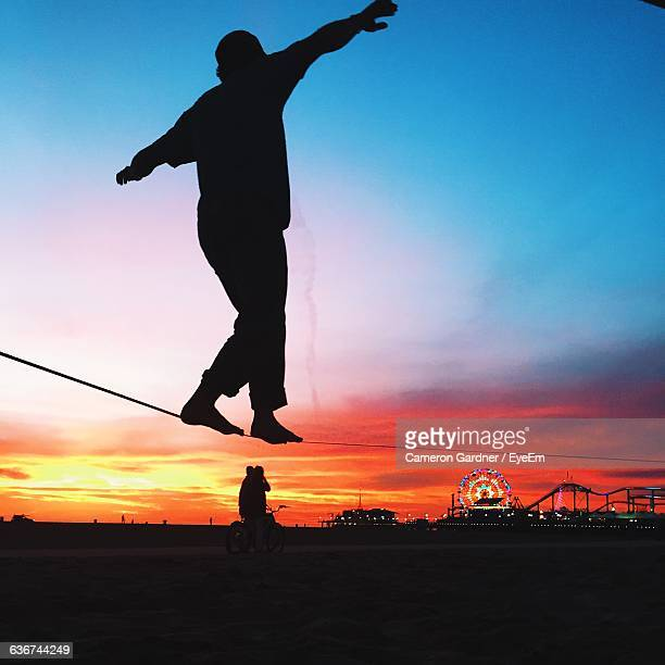 silhouette man performing slackline at beach against sky during sunset - santa monica stock pictures, royalty-free photos & images