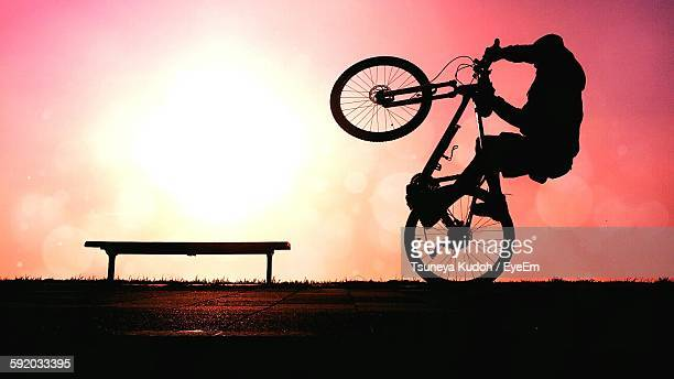 Silhouette Man Performing Wheelie During Sunset