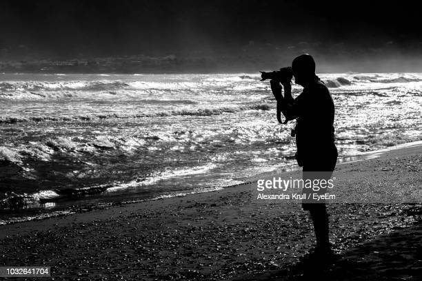 Silhouette Man Photographing At Beach