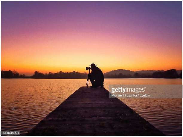 silhouette man photographing on pier over lake against sky during sunset - michael hruschka stock pictures, royalty-free photos & images