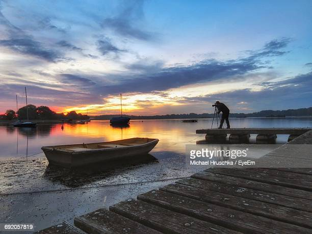 silhouette man photographing while standing on jetty against sky - michael hruschka stock-fotos und bilder