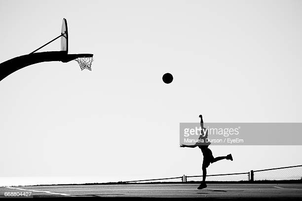 silhouette man playing basketball on court against clear sky - shooting baskets stock pictures, royalty-free photos & images