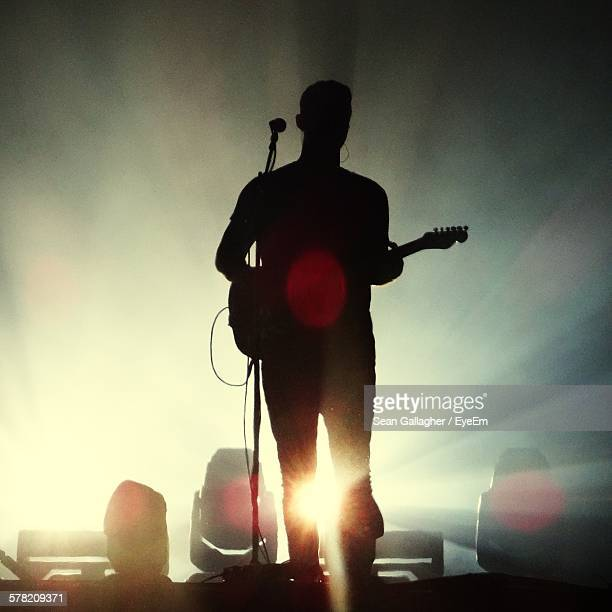 Silhouette Man Playing Guitar On Stage In Concert