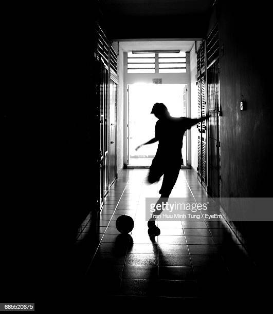 Silhouette Man Playing Soccer In Passageway