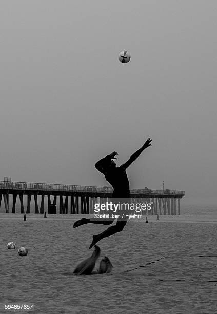 silhouette man playing volleyball at beach against clear sky - hermosa beach stock pictures, royalty-free photos & images