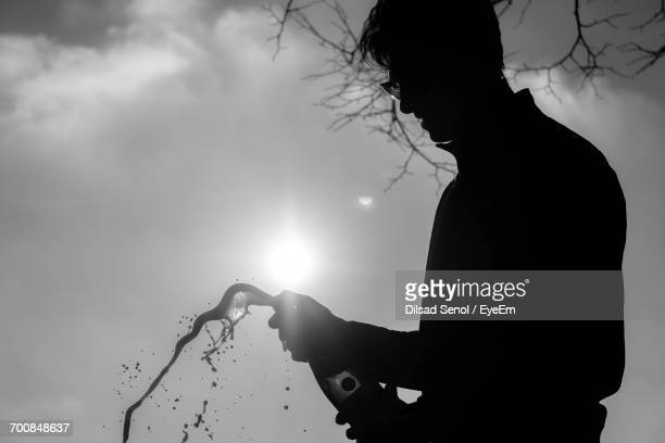 Silhouette Man Popping Champagne While Standing Against Sky On Sunny Day
