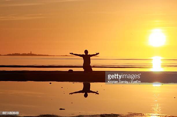 Silhouette Man Practicing Yoga At Sea Shore Against Sky During Sunrise