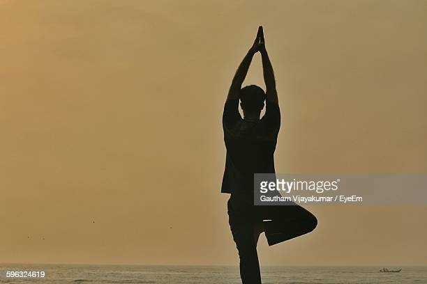 Silhouette Man Practicing Yoga By Sea Against Sky During Sunrise