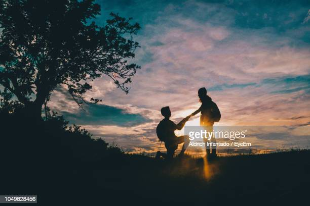 silhouette man proposing girlfriend against sky during sunset - fidanzato foto e immagini stock