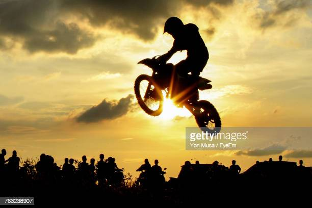 silhouette man riding bicycle against sky during sunset - motocross fotografías e imágenes de stock
