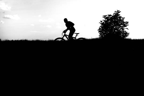 Silhouette Man Riding Bicycle  Against Sky