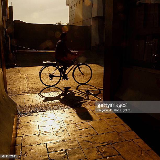 silhouette man riding bicycle on sunny day - malabon stock pictures, royalty-free photos & images