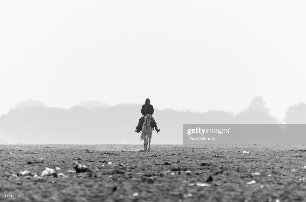 Silhouette Man Riding Horse At Varanasi : Stock Photo