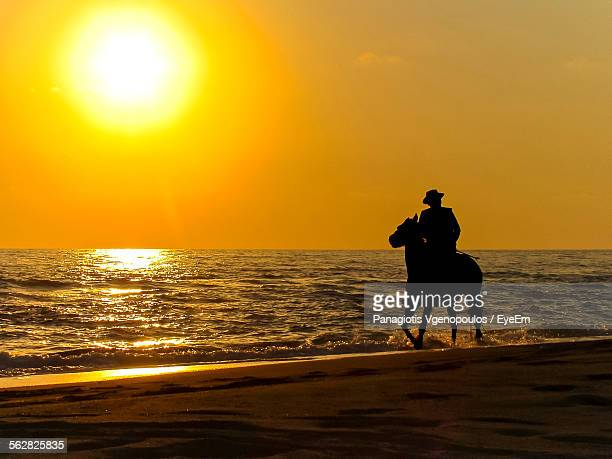 silhouette man riding horse on beach against orange sky during sunset - vgenopoulos stock pictures, royalty-free photos & images