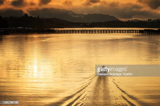 silhouette man sailing boat in lake to wooden bridge against sky during sunrise - カンチャナブリ県 ストックフォトと画像