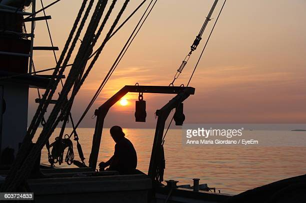 silhouette man sailing on fishing boat in sea against sky during sunset - anna fischer stock-fotos und bilder