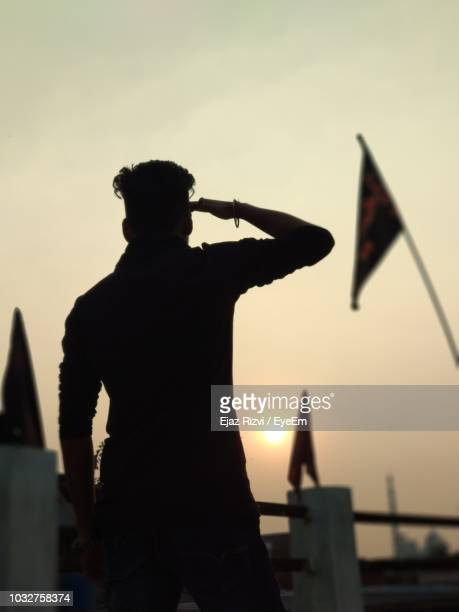 Silhouette Man Saluting Flag Against Sky During Sunset