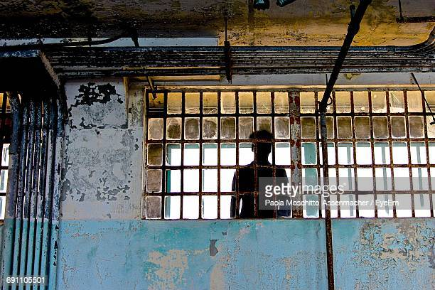 silhouette man seen through window in prison at alcatraz island - alcatraz stock photos and pictures