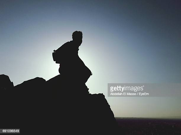 Silhouette Man Sitting On Mountain Against Clear Sky During Sunset