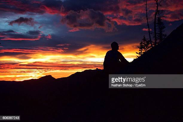silhouette man sitting on mountain against cloudy sky - nathan bishop stock pictures, royalty-free photos & images