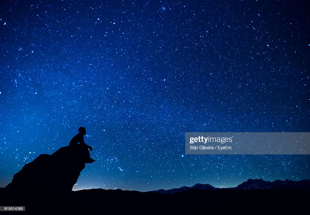 Silhouette Man Sitting On Rock Against Constellation In Blue Sky : Stock Photo