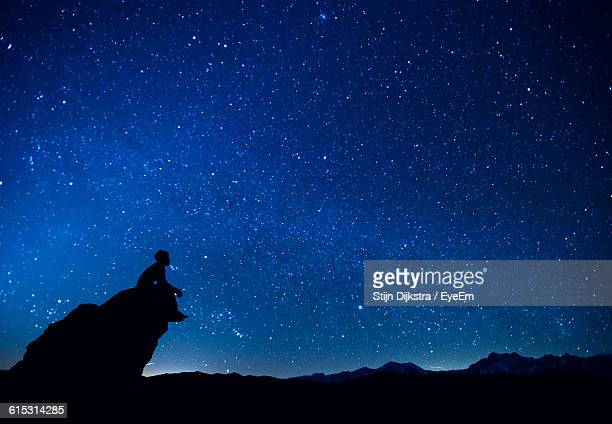 Silhouette Man Sitting On Rock Against Constellation In Blue Sky