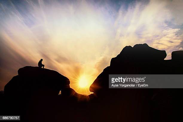 Silhouette Man Sitting On Rock Formation Against Cloudy Sky During Sunset