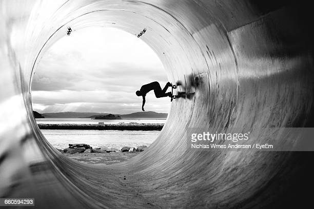 silhouette man skateboarding in cement pipe at beach - skating stock photos and pictures