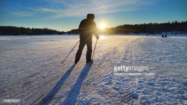 Silhouette Man Skiing On Snow Field Against Sky During Sunset
