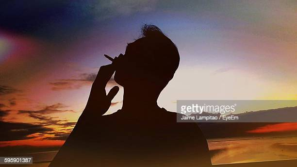 Silhouette Man Smoking Cigarette While Standing On Beach