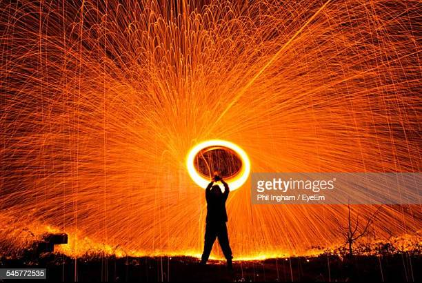 Silhouette Man Spinning Illuminated Wire Wool At Night