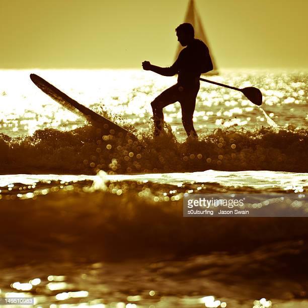 silhouette man stand up paddling - s0ulsurfing stockfoto's en -beelden