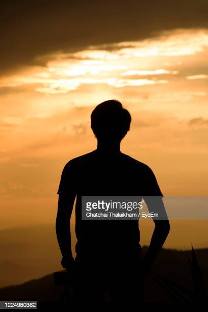 silhouette man standing against beautiful sunset - chatchai thalaikham stock pictures, royalty-free photos & images