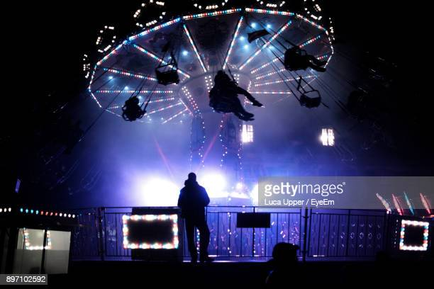 Silhouette Man Standing Against Illuminated Chain Swing Ride At Night
