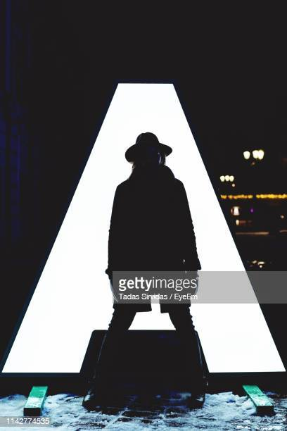 silhouette man standing against illuminated letter a at night - letter a stock pictures, royalty-free photos & images